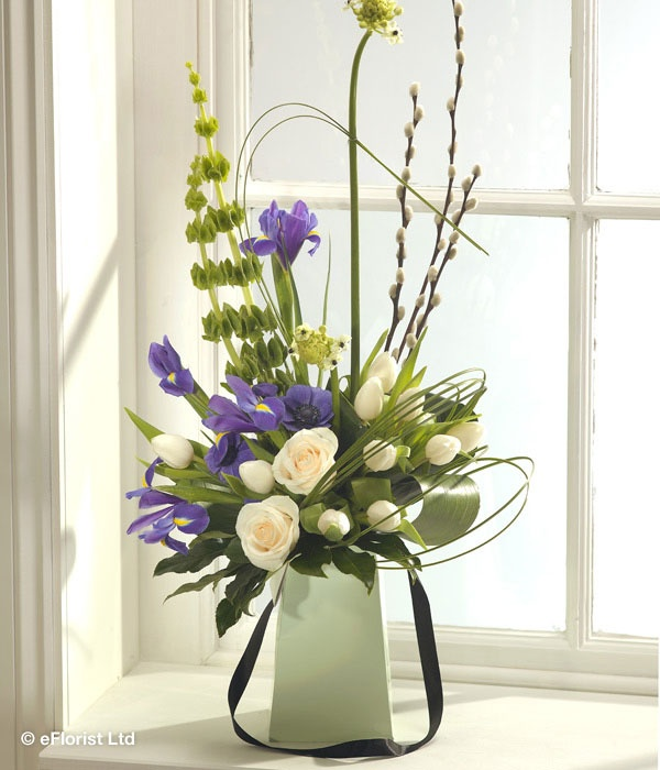 Pretty Pastures - A striking and incredibly elegant flower gift vase arrangement. Pure creamy white Roses, Chincherinchee and Tulips have been expertly married with bold Iris and Anemone blooms. Tall sprigs of Pussy Willow and Molucella complete this sophisticated flower display.