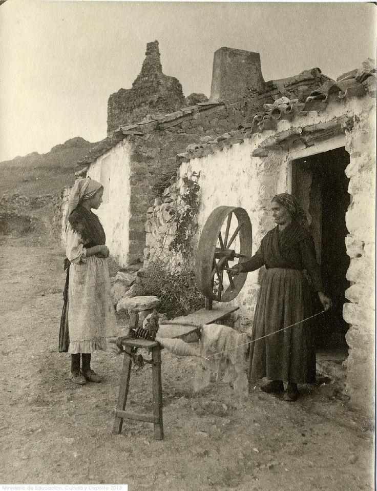 Spinning wool on the great wheel. Spain, 1917 Imagen de dos mujeres an la puerta de su casa; una de ellas está hilando con la rueda de hilar y la otra contempla la escena. http://ceres.mcu.es