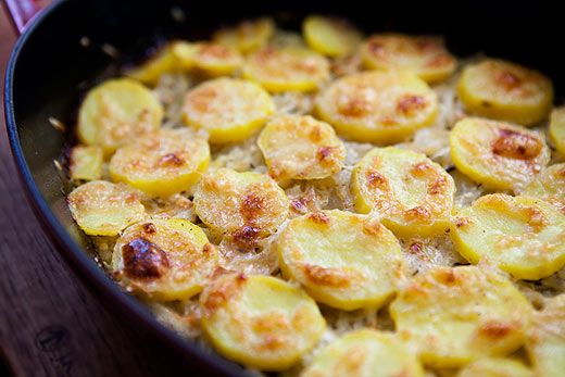Onion potato gratin with sliced Yukon Gold potatoes, baked with onions, with heavy cream and Gruyere and Parmesan cheeses.