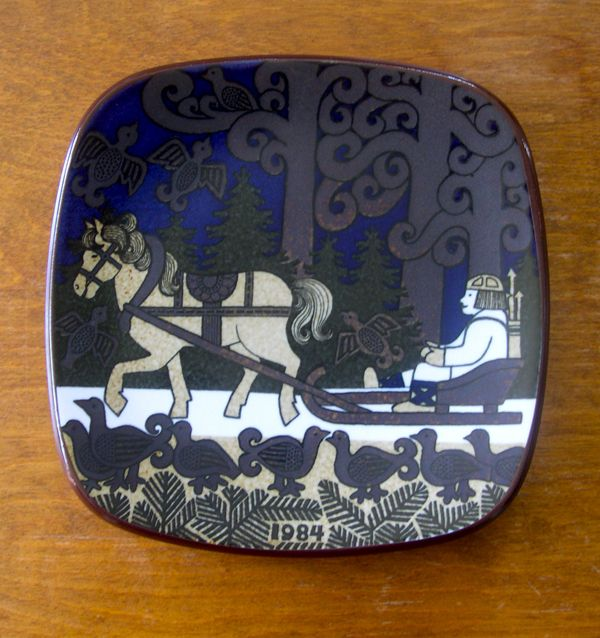 The picture shows Lemminkainen in his sleigh drawn by a horse. There are birds in the trees, the sky and on the ground.
