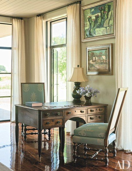 A prickly pear painting by Otis Dozier (top) hangs above an antique partners desk that once belonged to Senator Prescott Bush, one of George W. Bush's grandfathers; the antique chairs are French
