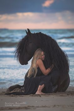 Girl hugging sitting horse on the beach. Beautiful sunset photography, night is falling and it is getting dark, so pretty. Black Freisan and girl in black dress, surf is just beyond them with the waves breaking and view of ocean in the background. I love this pic!. Please also visit http://www.JustForYouPropheticArt.com for colorful inspirational art. Thank you so much! Blessings!