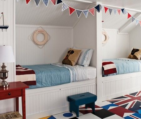 Regatta themes and nautical designs resonate in this bedroom. Perfect for children and cosy bed nooks with bunting and custom-painted nautical flags bring the room's charm from kitschy to classic.