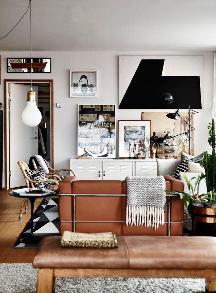 Det öppna rummet löper längs den stora altanen och i bortre änden ligger Gerthel.vardagsrumsdelen. Vit soffa Ghost av Paola Navone, Gervasoni. Den mindre i ljust läder är Petit Comfort av Le Corbusier. Den stora grafiska målningen är av Arne Ohlsson, affisch av Clay Ketter och fotografiet ovanför är av Joseph Beuys. Vita plåtskåp från Ikea. Den trearmade lampan är köpt på Olsson & Gerthel.