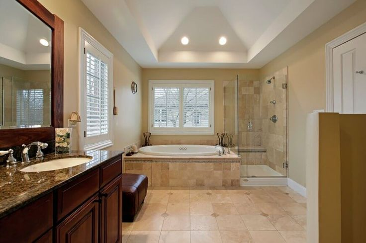 A drop-in bathtub with a marble tile platform and a glass enclosed shower in a spacious bathroom.