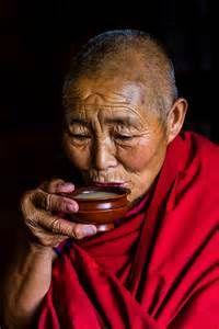 Buddhist nun drinking yak butter tea, Drepung Monastery, Tibet.