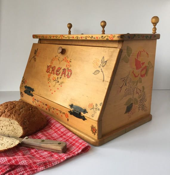 Large vintage wooden bread box stained a light brown and embellished with stenciled folk art roses, hearts and garlands, reminiscent of traditional Scandinavian and Pennsylvania Dutch décor. Three wooden finials with ball tops and two brass tacks along the back make this bread box stand out from the rest. The wooden knob on slanted drop-down lid, rustic hammered metal hinges and stenciled floral heart with the word Bread in front say farmhouse décor. The muted reds, greens and golds give the…