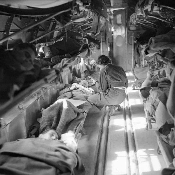 Medical Transport: Interior of a C 47 air ambulance flying between Catania, Italy to the General Hospital in Tunis, Tunisia. US Army nurse, Miss Mary Smith, is taking particulars from the patient during the flight. These men had started their journey at a Casualty Clearing Station (CCS) at Forgia.