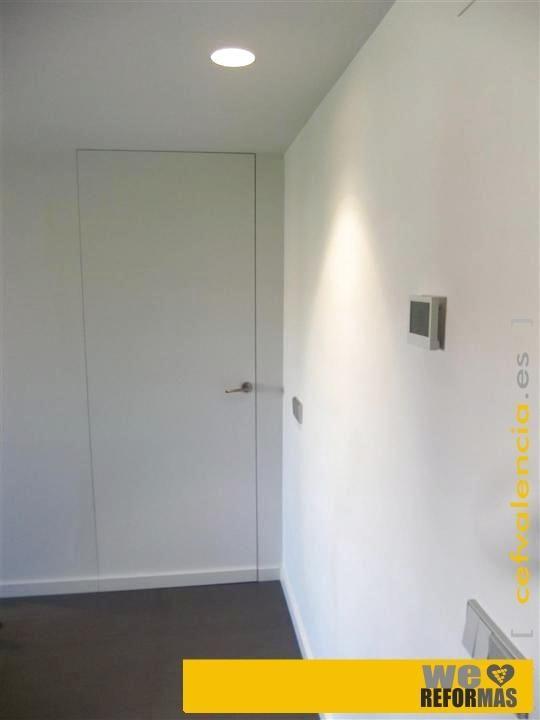 """Detalle de entrada hacia zona de noche con puerta """"raso-muro"""" perfectamente integrada en pared.  Más fotos de esta REFORMA INTEGRAL en:  www.cefvalencia.es/galeria/fotos-galeria-reforma-integral-valencia.html"""