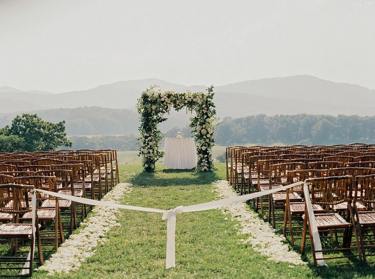 Outdoor wedding ceremony with floral wedding arch at Pippin Hill Farm & Vineyards | Photographer: Laura Gordon