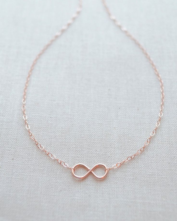 Tiny Infinity Necklace in silver, gold or rose gold. This petite handmade infinity charm looks great layered and is a beautiful symbol of love. By Olive Yew.