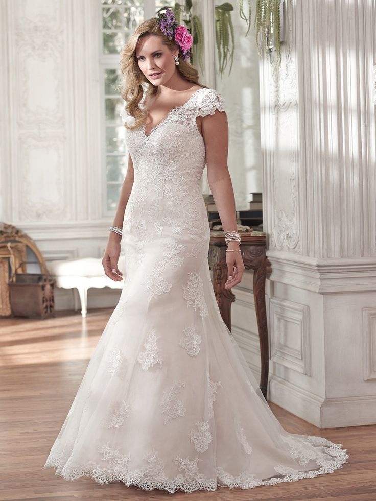 Pilar plus size wedding dress by Maggie Sottero |  Completely timeless is this slim A-line wedding dress. Constructed of delicate lace and ethereal tulle, this gown features scalloped trim adorning the V-neckline and plunging back. Complete with dainty lace sleeves. Finished with covered button over zipper back closure.