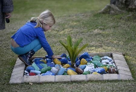 """A young girl looks at stones inscribed with """"get well"""" messages left outside the home of former President Nelson Mandela in Johannesburg"""