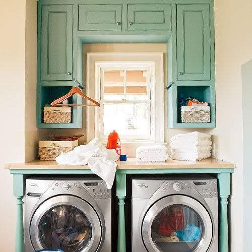 Laundry nook with built in cabinets and a folding spot.