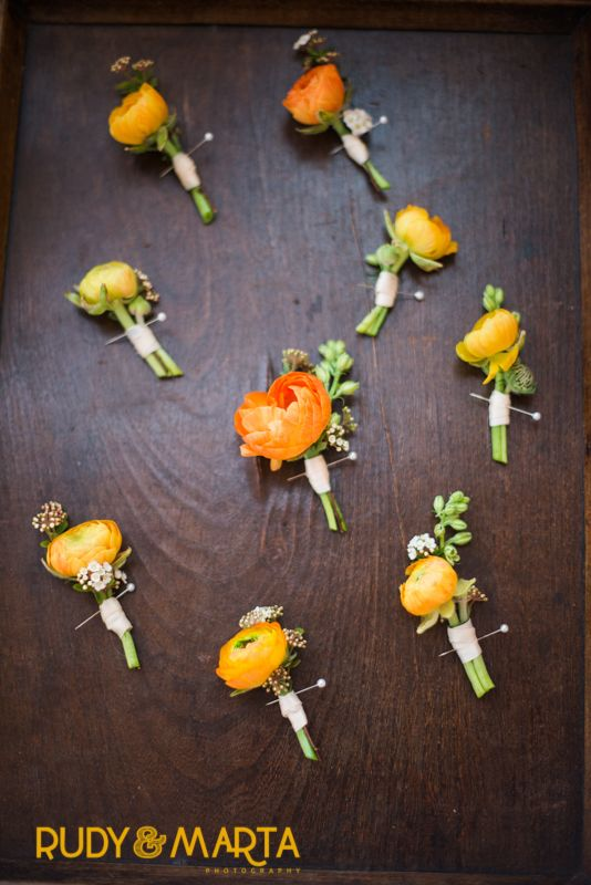 boutonnières of orange ranunculus paired with various buds of rice flower, spirea and larkspur.