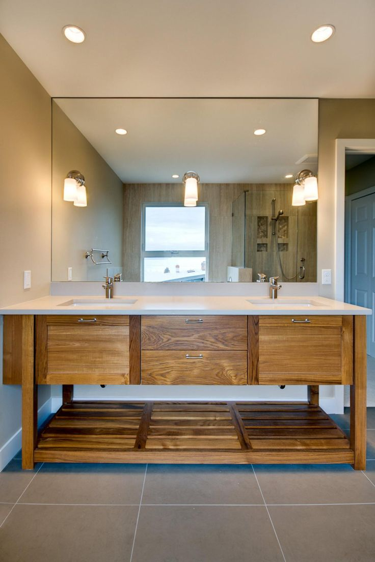 A streamlined teak wood vanity boasts sleek white countertops. The wood accent wall complements the exposed wood grain of the double vanity. Minimalistic chrome faucets and simple sconces on the bathroom mirror create a simplistic design.