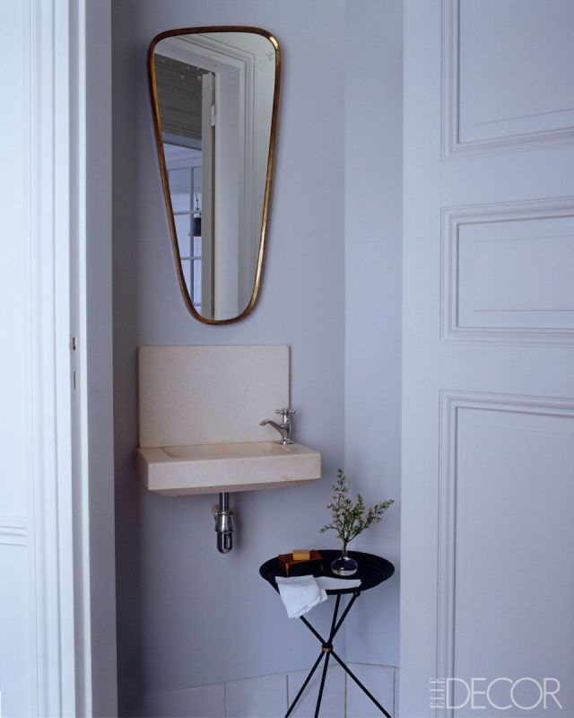 A circa-1950 brass mirror hangs in the powder room of the Paris pied-à-terre shared by designer Steven Volpe and his business partner, Roth Martin, who helm the San Francisco gallery Hedge. The French collapsible tripod table is vintage.   - ELLEDecor.com