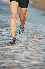 Beautiful young athletic woman running on the beach. She is listening music. by Eduard Bonnin Turina - Stocksy United - Royalty-Free Stock Photos