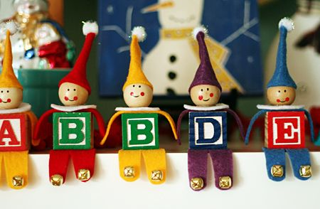 I seriously cannot stop taking pictures of these super-cute alphabet block elves! When I saw these elves at that artist woman, I knew we just had to make them. We followed the great step-by-step directions at that artist woman, except for the heads. I had a couple packs of wooden face beads in my stash and they were perfect for this project. (I found them