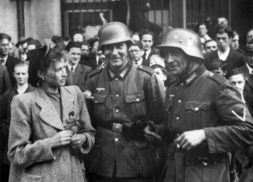 A woman looks skeptical at two German soldiers, Netherlands 40
