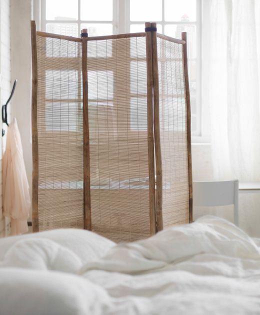 Un paravent en bambou dans une chambre.