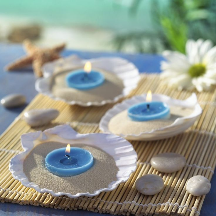 Centerpieces on bamboo/wood placemats with shells & sand & candles