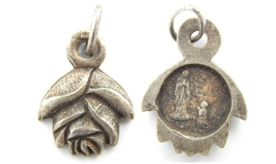 Here is a lovely rose shaped Catholic medal depicting the grotto where Saint Bernadette saw Our Lady of Lourdes. This medal is a heavy silver tone metal - NOT aluminum. (Click ZOOM to ZOOM in)  ~We DO NOT sell Vintage/Antique Reproductions. Everything we sell is authentically antique or vintage. We sell a few jewelry supplies, and those are listed as such.~  Measures:  7/16 - Medal (closed, not including bail) or 11mm 3mm - Jump Ring  NOTE: Picture 1 is of the front and backside - listing is…