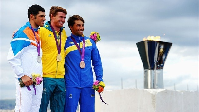 Gold medallist Tom Slingsby (C) of Australia celebrates silver medallist Pavlos Kontides (L) of Cyprus and bronze medallist Rasmus Myrgren (R) of Sweden following the Men's Laser Sailing on Day 10 of the London 2012 Olympic Games at the Weymouth & Portland venue