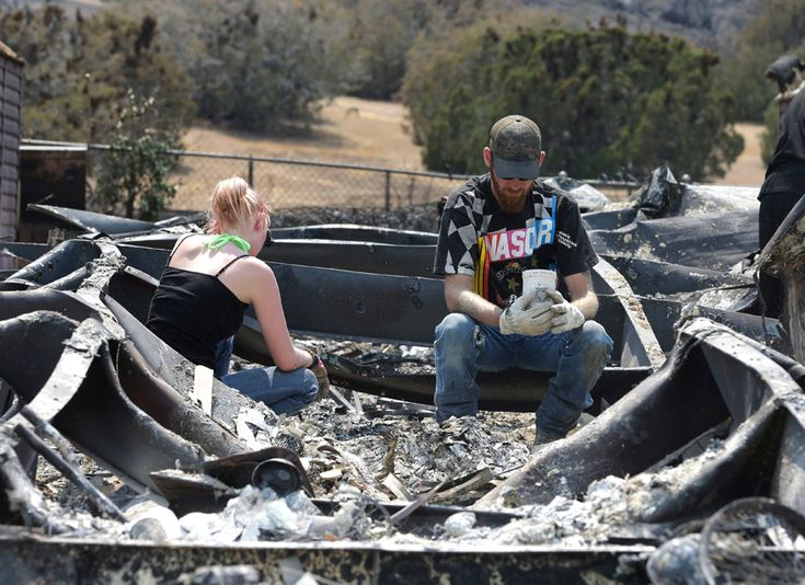 Lucas Martin stares at a cup found in the ashes of his fire ravaged home in South Lake, California, Sunday, June 26, 2016. Martin's home was among the more than 200 homes and buildings destroyed by the fire that swept through the area near Lake Isabella, California, At right is Emily Fryer who help Martin sift through the rubble.   Rich Pedroncelli / AP