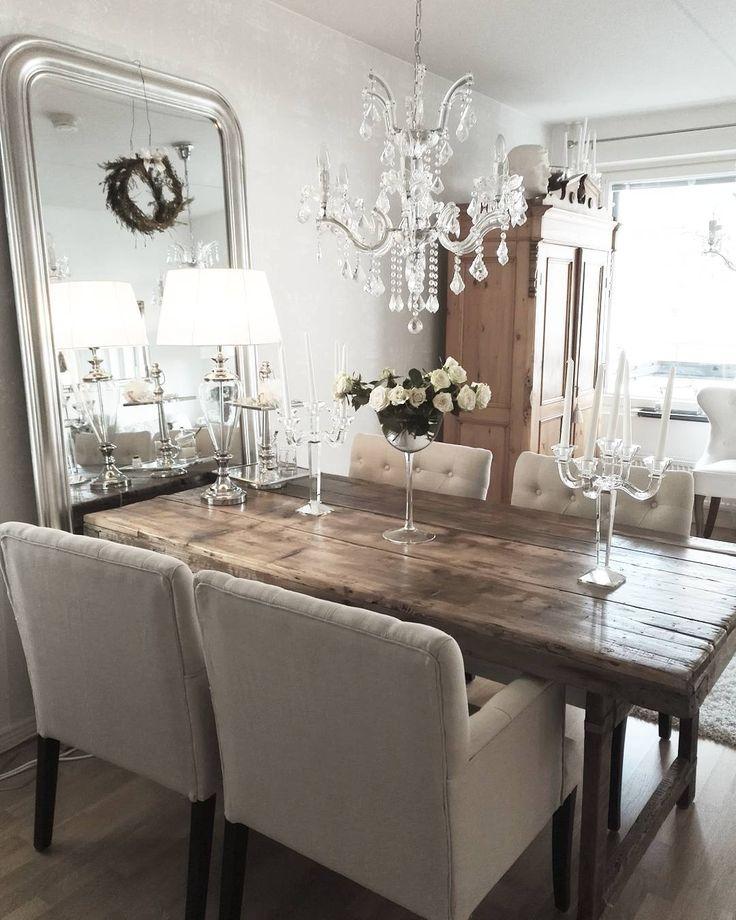 Vanha puinen pöytä, kauniisti kimalteleva kristallivalaisin ja korkea peili luovat monipuolisen kattauksen tilan tunnelmaan.
