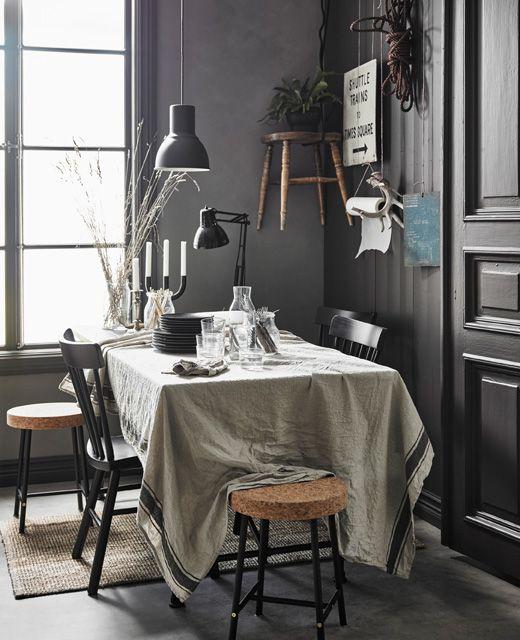 Grande table de salle à manger couverte de documents, avec nappe en lin et assiettes couvrant le reste