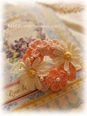 mieですお花のブローチですFlowergardenシリーズのカモミールを少しアレンジしてお花を編みましたやさしいオレンジやサーモンピンクのお花をちりばめ...