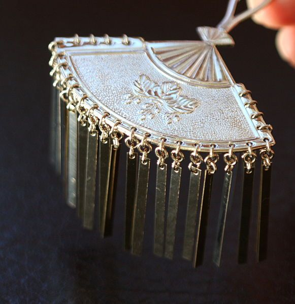 Ōgi - Also called Princess style, are metal, fan-shaped and kamon-imprinted kanzashi with aluminum streamers held in place by a long pin. These are usually worn by maiko in the hair just above the temple.