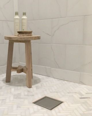 """Hello Lovely's Chicagoland whole house DIY renovation includes this serene white tiled shower in master bathroom with carrara herringbone mosaic shower floor, white porcelain wall tile called """"Calacatta"""" (Lowes), rustic wood 3 leg stool, and Aveda hair products/Hello Lovely Studio/fixer upper"""