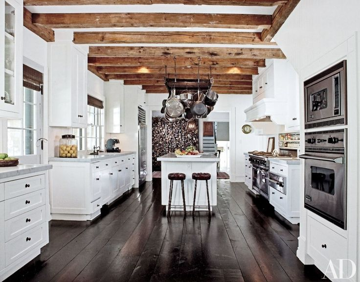 At his home in Amagansett, New York, talent agent Sandy Gallin warmed up a white kitchen with reclaimed-timber beams and lined the floor in dark wood planks | archdigest.com