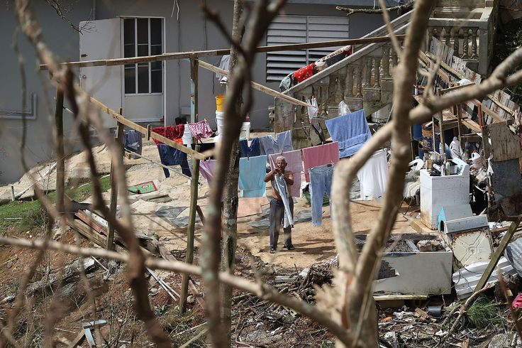 A man hangs laundry as people wait for the electrical grid to be repaired in Progreso Barrio Pulguillas, Puerto Rico.