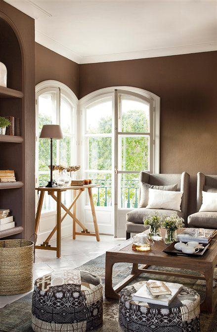 Salón con paredes color chocolate y ventanas en arco