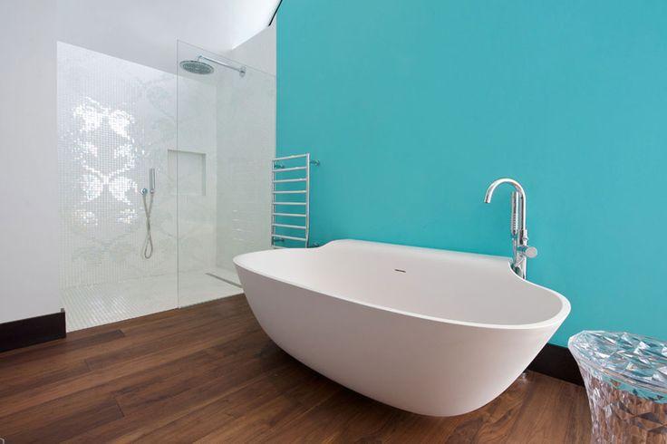 In questo bagno minimal chic la vasca mozzafiato spicca fortemente davanti alla parete di colore blu turchese