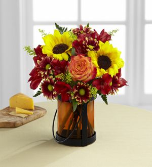 Giving Thanks - Exuding a superior warmth and sophistication, this gorgeous flower bouquet will be just the gift to send to become a part of your special recipient's fall celebrations! Stunning sunflowers are bold and beautiful when combined with bi-colored orange roses, red Peruvian lilies, yellow solidago, burgundy traditional daisies and lush greens, perfectly brought together to create an unforgettable flower bouquet.