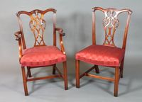 A set of 12 Chippendale style mahogany dining chairs, late 20th Century, two having arms, with foliate carved cresting rails  above scroll carved and pierced vase splats, having red striped  damask upholstery, raised on frog back moulded and chamfered  legs SOLD FOR £900
