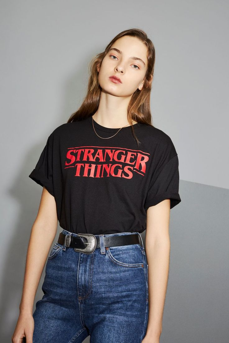 Merchandise gets a modern update with our Stranger Things collaboration. This black tee features the show's iconic red logo. We're styling it tucked into retro-inspired jeans for an on-trend eighties look.