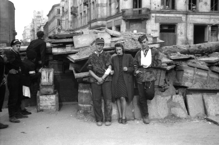 """Polish Resistance fighters of the """"Narocz"""" Platoon, """"Parasol"""" Battalion of the Polish Home Army (Armia Krajowa) guard a barricade on Sienna Street during the Warsaw Uprising. The Uprising was timed to coincide with Soviet forces approaching the..."""