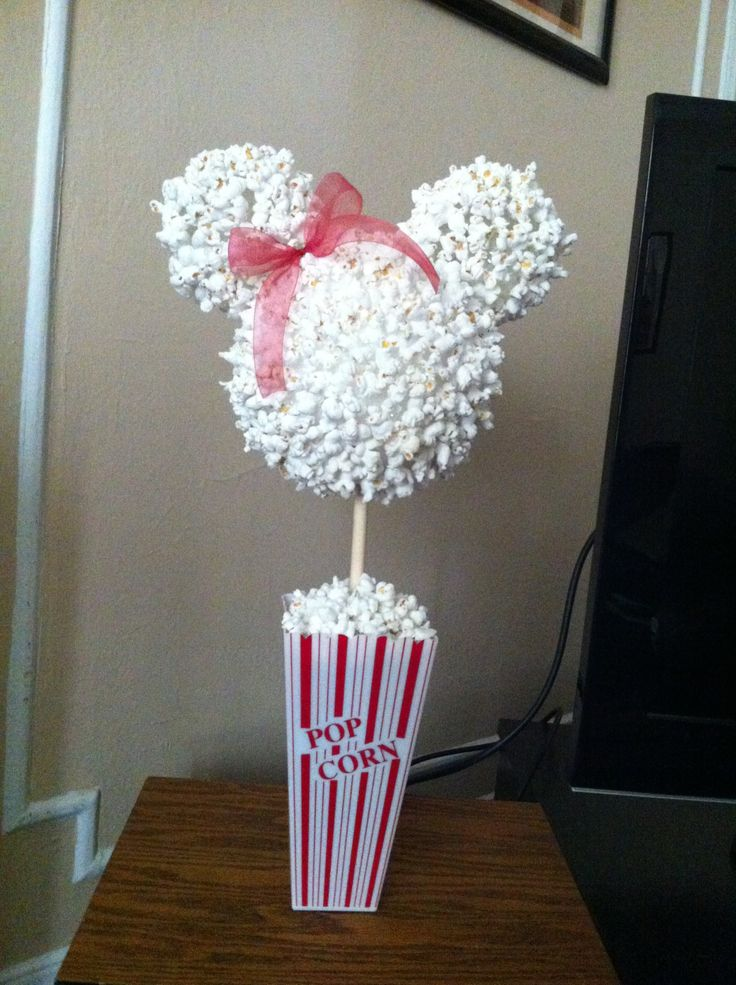 The Perfect Decoration for your Disney Themed Party!    NEEDED:  Plastic Popcorn Container * Floral Foam * Wooden Dowel * White Styrofoam Craft Ball * 2 Create-Your-Own Ornaments (with metal tops removed) * Hot Glue * Popcorn * Ribbon (optional)