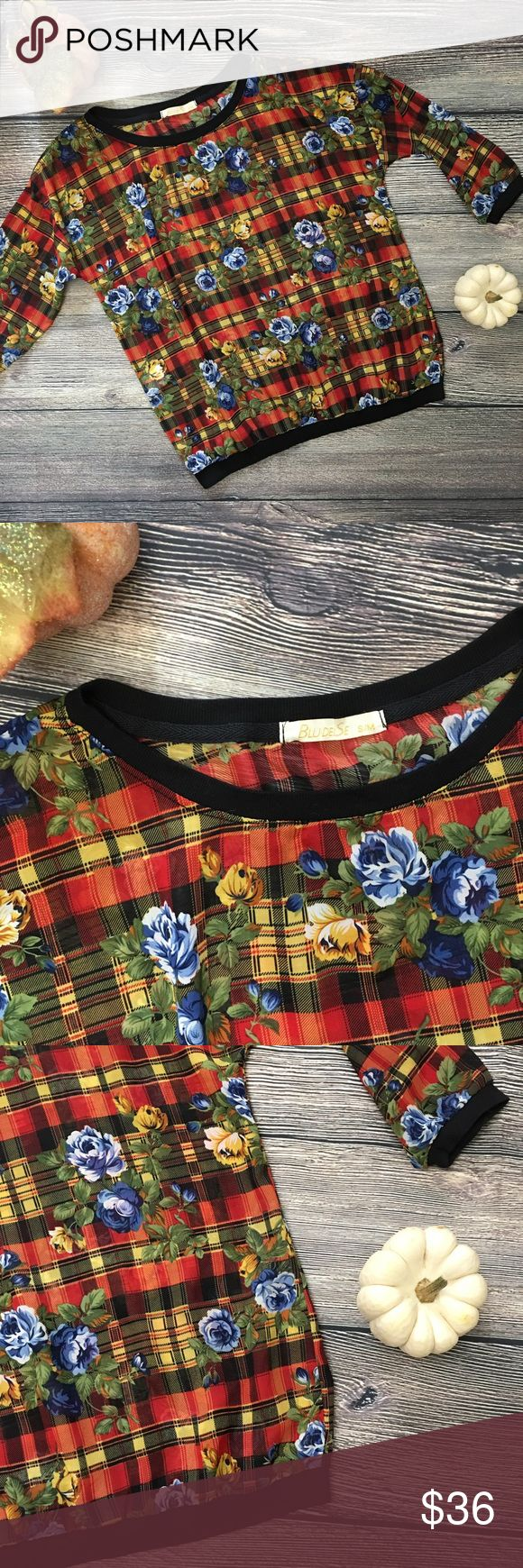 """Euro NWOT Blu Del Se plaid floral blouse sz S/M Purchased in Europe Boutique, lightweight semi-sheer blouse is a great pop of color. New without tags, red/yellow/black plaid accented with blue/yellow flowers. rounded crew collar, hem & sleeves are banded in black ribbing to give lightweight shell structure. wear this piece with a nude bra or throw on a tank underneath. Let it peek out of a black buttoned blazer over jeans. Cotton/Elastane. Approximately 20 1/2"""" bust/pit to pit, 23"""" length…"""