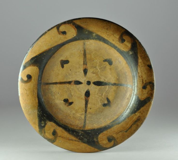 Etruscan Genucilia plate, 4th century B.C.  Etruscan Genucilia plate,decorated with a four pointed star on the shallow floor and dots in the interstices, the narrow bulged rim enhanced with five spiral waves, 14.2 cm diameter. Private collection