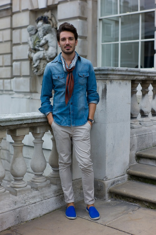 Wardrobe staples simply styled for #LFW to underscore the importance of good quality basics for men. Slim-leg chinos, a well-loved denim shirt, and espadrilles are tied together with a vintage silk scarf for a late summer look that creates a resort feel using popular commercial shapes. WGSN street shot, London Fashion Week