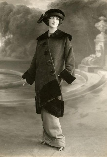 Ladies' fashion. Fashion model showing Paris winter fashion 1912. Walking costume consisting of a slender cut dress and a coat done up diagonally, trimmed with a fur collar, cuffs and seem. Studio-photography, France, 1912