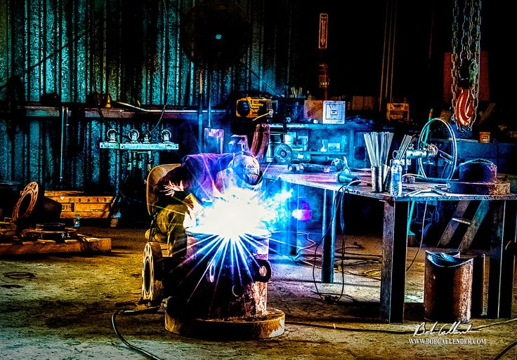 In the photograph, Fusion, the welder sits in his shop