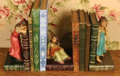 """Hide-and-Go-Seek Bookends      Three do the job even better than two...especially when engaged in the generations-old game in which the """"counter"""" puts her nose to the books of your library collection. Painted faux bronze. 6½ x 3½."""