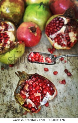 Open pomegranate on the table and spoon with red beans, rustic